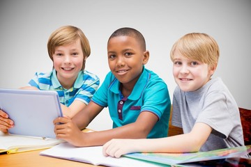Composite image of cute pupils using tablet computer in library