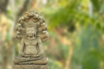 Common buddha image in meditation pose with naga on guard in the back of Buddha image over outdoor park