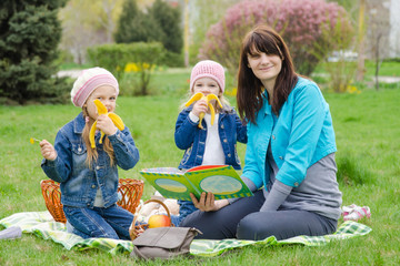 Two girls eating a banana on a picnic