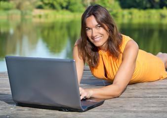 Frau mit Notebook / Laptop am idyllischen Weiher