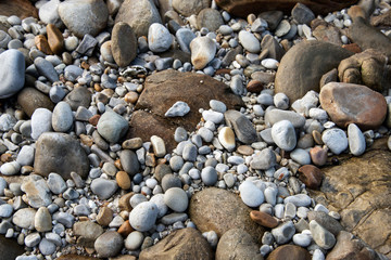 A close up of rocks and pebbles on a beach