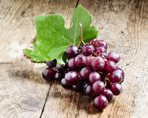 Round purple grapes with leaves on the old wooden table, selecti