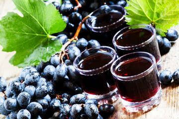 Fresh dark grape juice and fresh berries on old wooden table, se