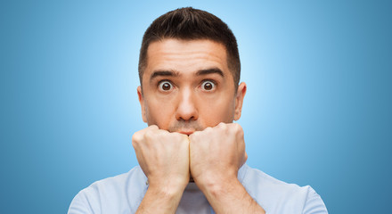 scared man face over blue background