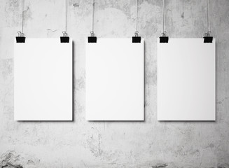 three blank poster hanging on a white background painted walls