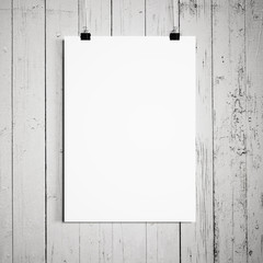 blank poster hanging on a white background a wooden wall