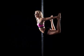 Junge Frau macht Poledance an der Stange