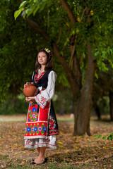 Girl in bulgarian costume in the park