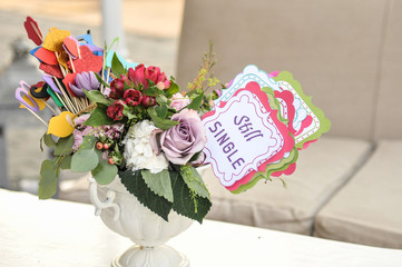 """Multicolored fresh flowers bouquet and paper decorations in a vase on a table and tag with words """"still single"""""""