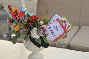 "Multicolored fresh flowers bouquet and paper decorations in a vase on a table and tag with words ""still single"""