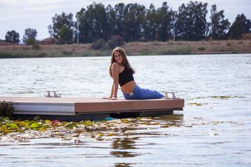 Adolescente de 15 años en el embarcadero. Chica rubia adolescente pasando una tarde de verano junto al rio.