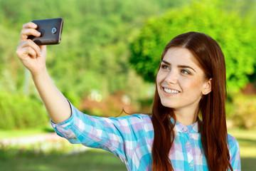 Beautiful girl taking selfie in the park