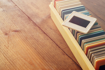 close up image of old slides frames and old camera over wooden table