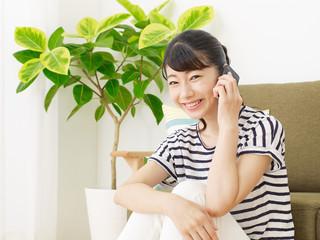 部屋でスマートフォンで話す女性