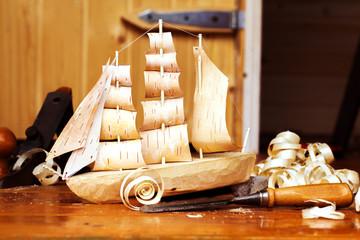Wooden ship toy workshop carpenter with a plane, chips, birch