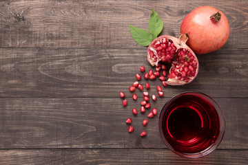 Ripe pomegranates with juice on wooden background