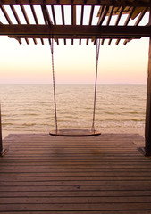 Swing at the sea on sunset time.