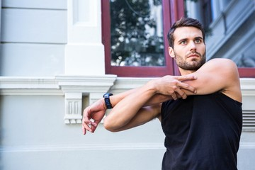 Handsome athlete stretching his arm