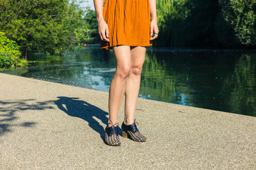 Legs of young woman standing by pond in park