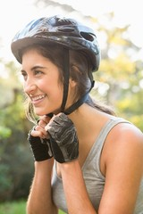 Smiling athletic brunette putting on helmet