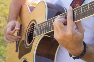 Man's hands playing acoustic guitar outdoors