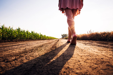 woman goes barefoot at sunset on field road