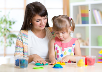 Young woman and kid playing with colorful clay molding different