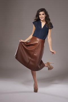 Charming girl in elegant leather skirt