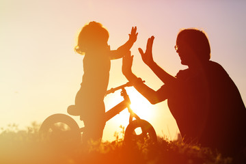 father and daughter having fun riding bike at sunset