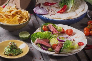Mexican tortillas with green fresh salad filling, beef, onions, tomatoes with gucamole and tortilla chips on te vintage board