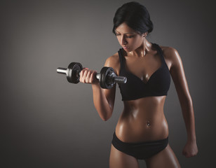 sporty muscular woman working out with dumbbell on a gray backg