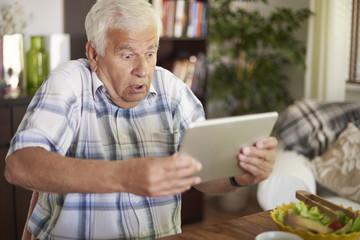Shocked senior man holding his tablet