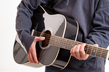 Close up of hands learning to playing an acoustic guitar