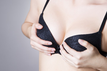 Big natural female breast in black bra