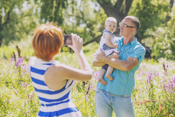 Family, mother, father and baby in nature photographed on the ph