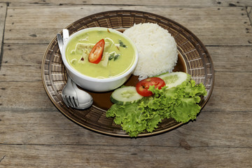 Thai green curry soup and some rice decorated on wooden background, Thai food.