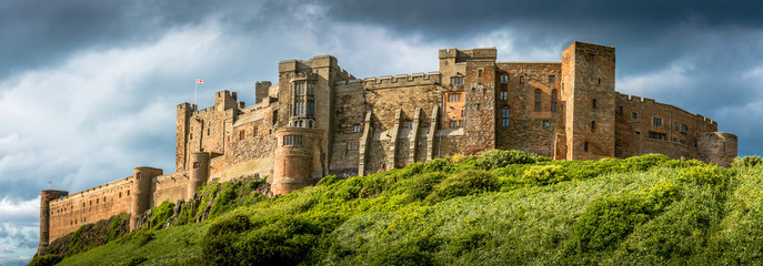A panoramic view of the west fortifications of Bamburgh Castle flying the English flag against a stormy sky.