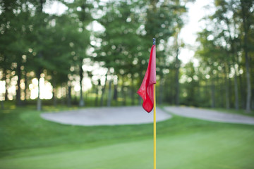 Red golf pin flag in front of defocused green