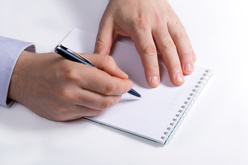 Businessman takes notes in a notebook. Hand writes a pen in a no