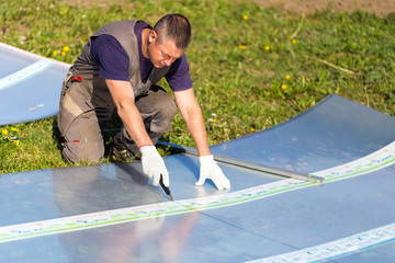 Worker in overalls with a knife cuts the polycarbonate sheet