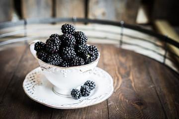 Blackberries in a mug on wooden background
