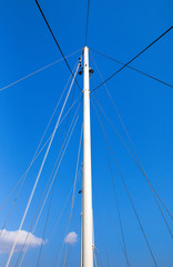 The mast of the ship on a blue sky background