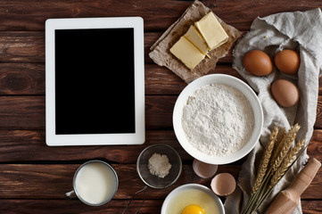 White tablet computer with blank screen with ingredients for making pancakes or cake - flour, egg, butter, milk on the wooden background. top view. rustic style. free space for text . Copy space