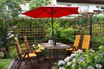 Wooden furniture with umbrella in backyard patio.