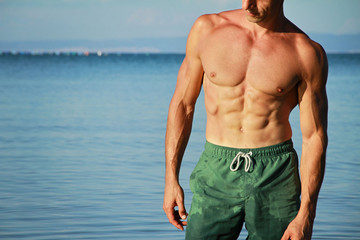 Strong muscular Men, perfect body, abs, six pack, sea, beach, swimwear