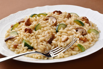 Dish of mushroom zucchini risotto with fork
