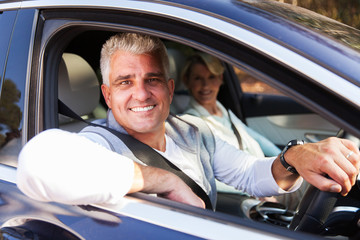 Fototapete - middle aged couple driving a car