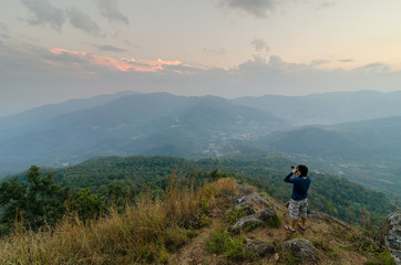 Photographer shooting the beautiful landscape of the Thailand evening mountains.