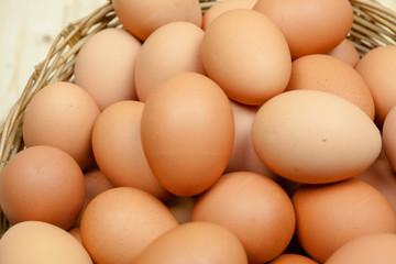 Full of Eggs put in a wicker basket in wooden background