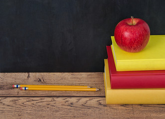 Stack of school books with apple and pencils on the desk